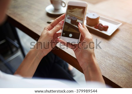Closeup of women's hands making photo of sweet dessert on mobile phone while sitting in comfortable restaurant, female taking pictures with cell phone camera of delicious pastry during rest in cafe - stock photo