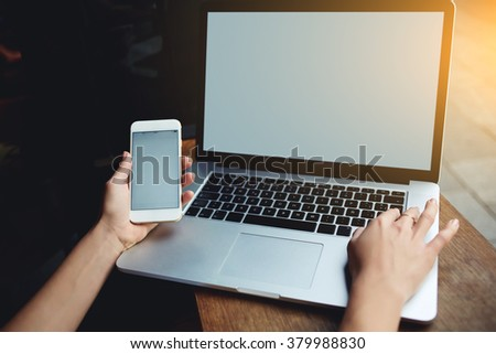 Closeup of women's hands using mobile phone and laptop computer with blank copy space screen for your advertising text message or content, female holding cell phone and keyboarding on net-book - stock photo
