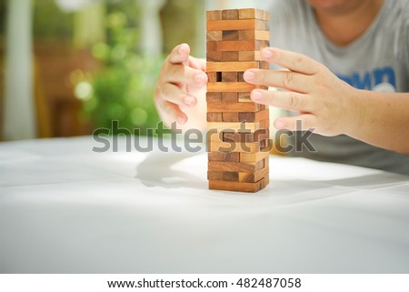Closeup of wood blocks stack game playing by asian man