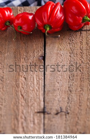 Closeup of wooden board with four round red chili peppers in row at top - stock photo