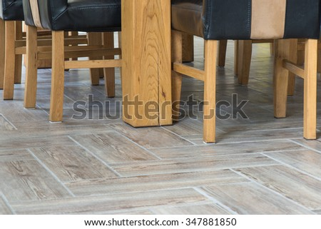 Closeup of wooden chairs and table legs on ceramic tile floor