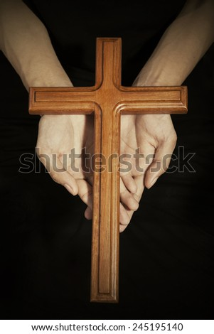 Closeup of wooden cross on the prayer palms, symbolizing christian person is praying - stock photo
