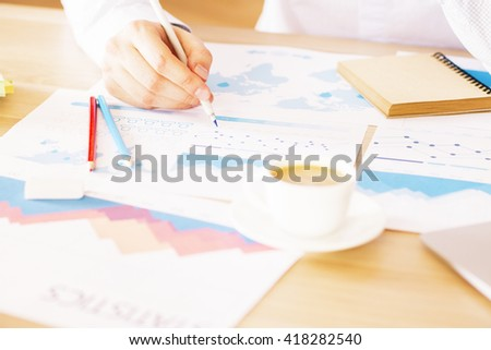 Closeup of wooden desktop with male analyzing business reports with schemes and graphs