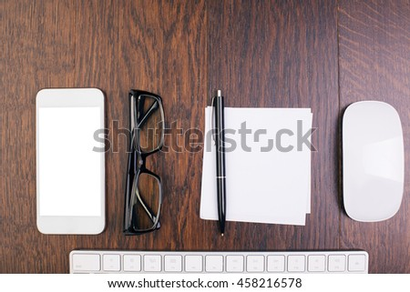 Closeup of wooden office desktop with blank white cellphone, glasses, piece of paper with pen, computer mouse and keyboard. Top view, Mock up - stock photo