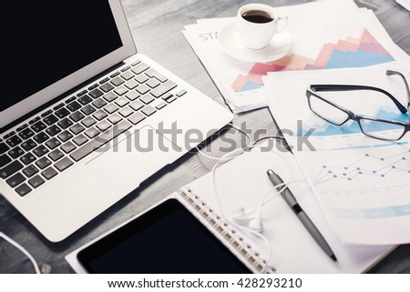 Closeup of wooden office table with blank white laptop screen, tablet, coffee, business report and other objects - stock photo