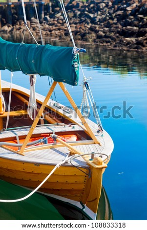 Closeup of wooden sailboat tied up at the dock with reflections