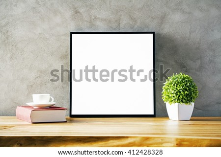 Closeup of wooden table with blank frame, flowerpot, coffee cup and book on concrete background. Mock up - stock photo