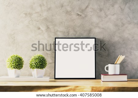 Closeup of wooden table with blank frame, two flowerpots, iron mug with pencils and book on concrete background. Mock up - stock photo