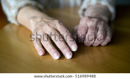 closeup of wrinkled old female hands resting on table
