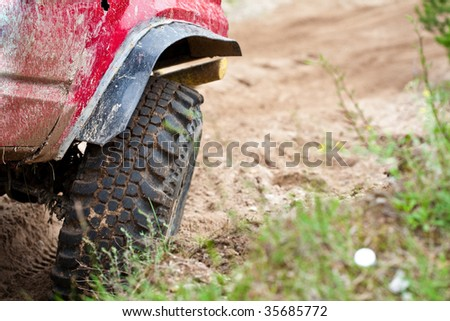 Closeup of 4x4 truck tire on sand track - stock photo