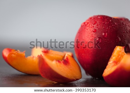 Closeup of yellow nectarine peach slices and whole fruit with water drops. Copy space. Shallow depth of field. - stock photo