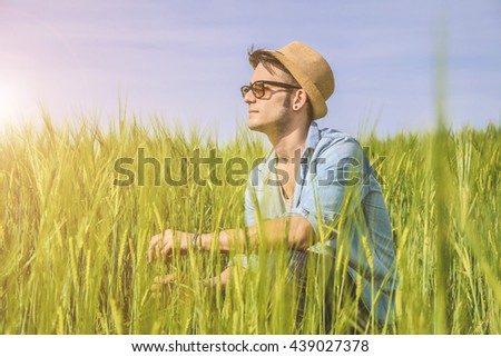 Closeup of young and caucasian man sitting,alone, in a countryside - lifestyle, people and nature concept - stock photo