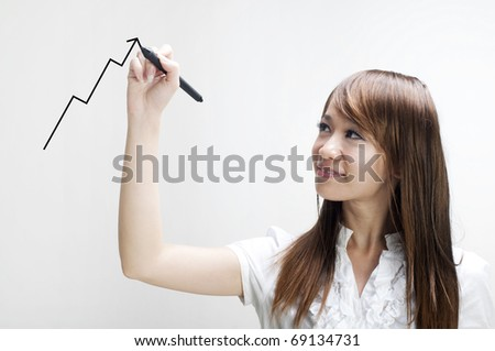 Closeup of young Asian business woman drawing graph on transparent glass or foil. - stock photo