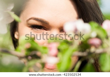 Closeup of young attractive woman looking thru blooming branches in the spring garden - stock photo