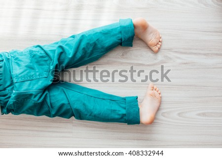 Closeup of young barefoot child with turquoise pants laying down on the floor - stock photo