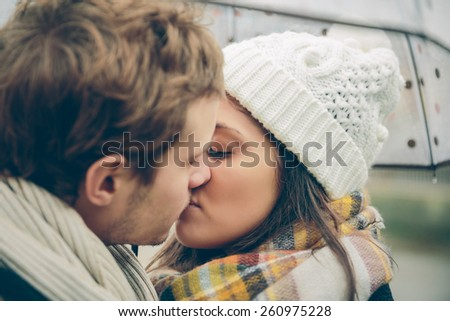 Closeup of young beautiful couple kissing under the umbrella in an autumn rainy day. Love and couple relationships concept. - stock photo