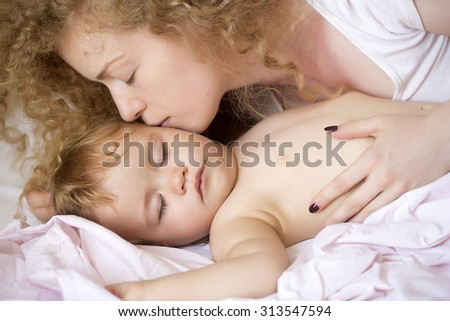Closeup of young beautiful loving lady with light blonde curly hair sleeping with little tiny cute male lovely baby indoor in bed with white linen lying close to each other, horizontal picture - stock photo
