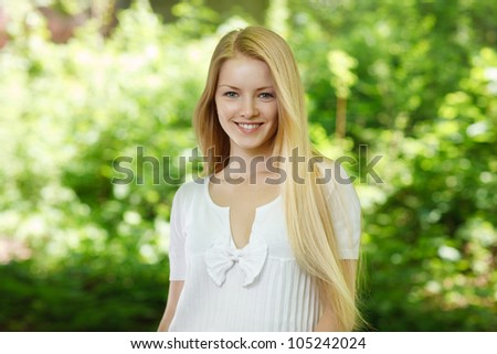 Closeup of young beautiful smiling blond woman, on green background of summer nature