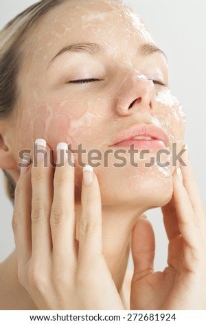 Closeup of young beautiful woman with gel exfoliation mask on face. - stock photo