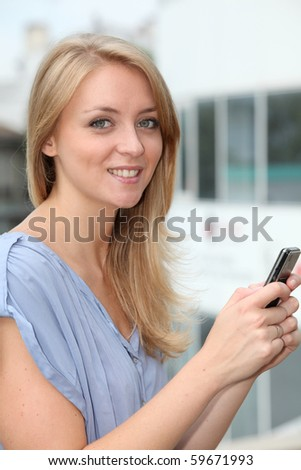 Closeup of young blond woman with mobile phone