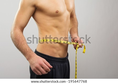 Closeup of young Caucasian man measuring his waist with tape measure. Gray background. Copy space available. Diet and healthy lifestyle concept. - stock photo
