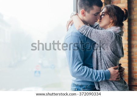 Closeup of young couple in love hugging close the window - stock photo