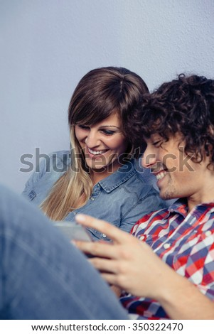 Closeup of young couple in love looking smartphones and laughing while resting over a bed. Leisure time at home concept. - stock photo
