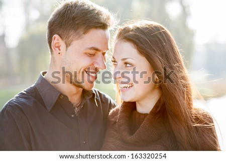 closeup of young couple outdoors laughing looking at each other - stock photo