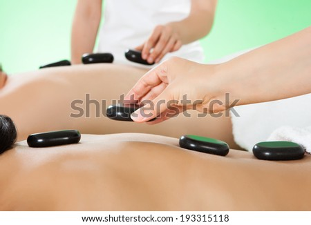 Closeup of young couple receiving hot stone therapy at beauty spa
