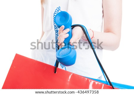Closeup of young customer holding gift or shopping bags and blue receiver isolated on white background - stock photo