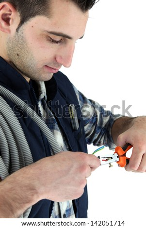 closeup of young electrician at work - stock photo