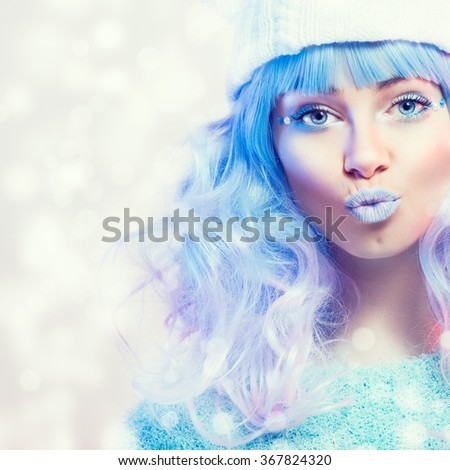 Closeup of young fashion woman with pastel blue hair, lips and eyes wearing beanie and mint green sweater. Makeup beauty portrait of female model blueish winter fashion style. Retouched, square format - stock photo