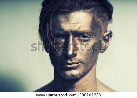 Closeup of young fashionable painted man model with bronze bodyart on face and stylish hairdo looking forward standing in studio on white background, horizontal picture