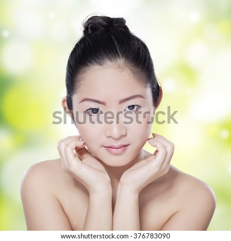 Closeup of young female model with black hair and smooth skin after skin care, shot in the studio