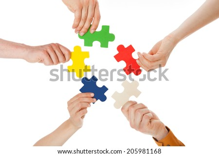 Closeup of young friends holding colorful jigsaw pieces over white background - stock photo