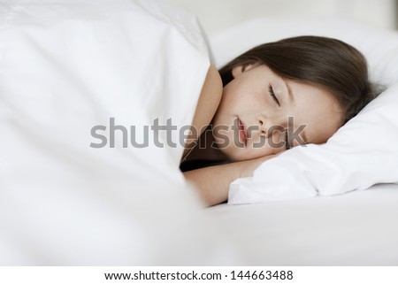 Closeup of young girl sleeping in bed cover with white blanket - stock photo