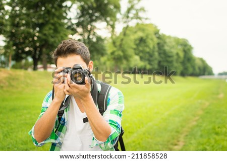 Closeup of young hipster man with digital camera outdoors. Young male photographer photographing nature on summer day. - stock photo