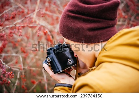Closeup of young hipster man with digital camera outdoors. Young male photographer photographing nature