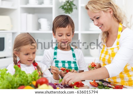 Closeup of young kids with their mother in the kitchen - preparing a healthy vegetables meal together