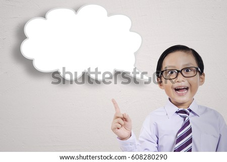 Closeup of young little businessman getting an inspiration while pointing an empty cloud bubble