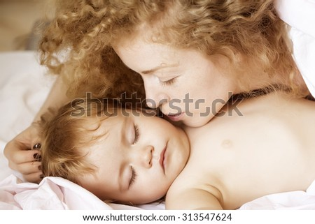 Closeup of young loving mother with light blonde curly hair sleeping with little tiny cute male lovely baby indoor in bed with white linen lying close to each other, horizontal picture - stock photo