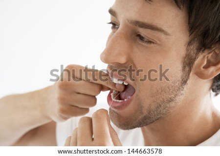 Closeup of young man flossing his teeth isolated on white background