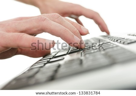 Closeup of  young man  hands typing on computer keyboard. Shallow depth of field.