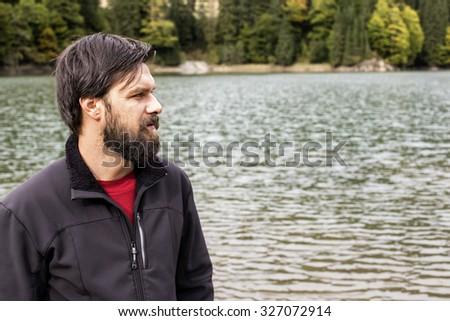 Closeup of young man near a mountain  lake looking in the horizon - stock photo