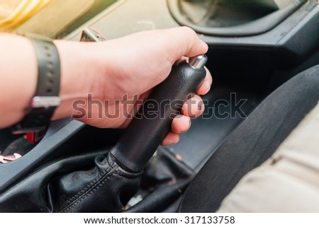 Closeup of young man pulling handbrake lever in car