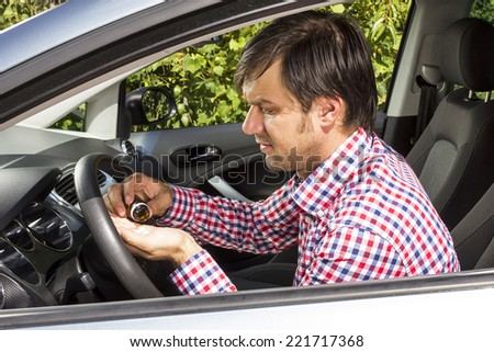 Closeup of young man taking pills inside his car - stock photo