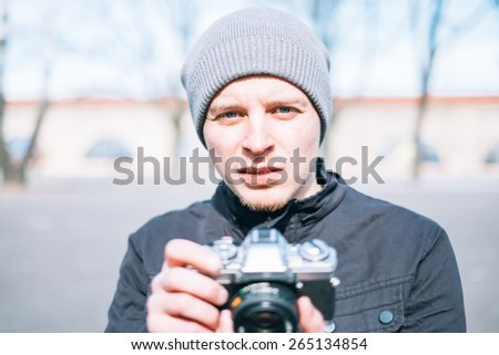 Closeup of young  man with digital camera outdoors. Young male photographer photographing nature - stock photo