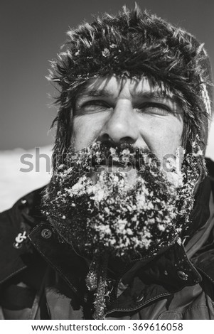 Closeup of young man with frozen beard into the mountains - stock photo