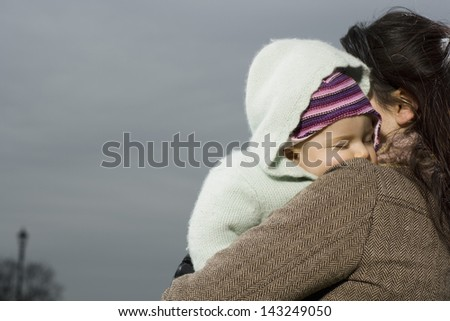 Closeup of young mother with baby sleeping in her arms - stock photo
