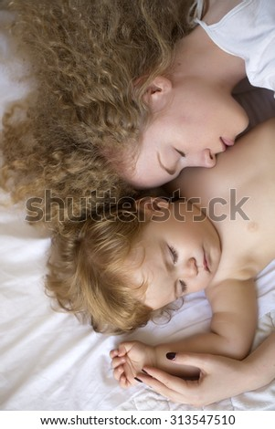 Closeup of young pretty loving mother with light blonde curly hair embracing small tiny cute male lovely baby sleeping indoor in bed with white linen lying close to each other, vertical picture